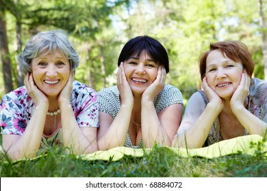 Portrait of three aged women resting on grass and looking at camera with smiles