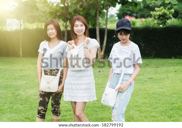 portrait of three asia young girl with bag on park, on outdoor