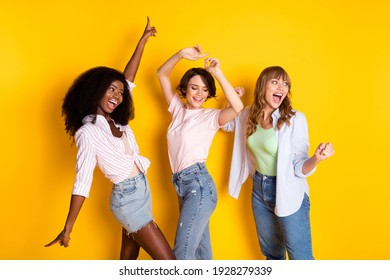 Portrait of three attractive cheerful girls dancing having fun rejoicing rest isolated over bright yellow color background
