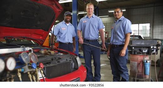 Portrait of three auto shop mechanics