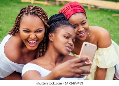 portrait of three beautiful african-american women afro braids dreadlocks and turban taking pictures of yourself on the phone in the park at a picnic,sisters on vacation