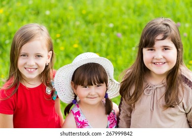 Portrait of three beautiful children having fun in the summer grass.