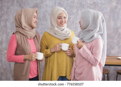portrait of three beautiful muslim woman standing while having a coffee time together