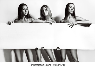 Portrait of three beautiful and sexy women holding a blank posing on white background