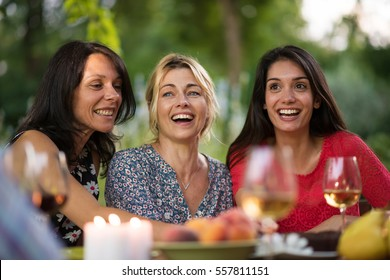 Portrait of three beautiful smiling women, they are gathered around a table on the terrace by a beautiful summer evening