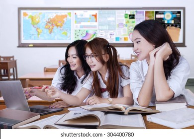 Portrait of three beautiful teenager students back to school and studying together in the classroom with laptop and books