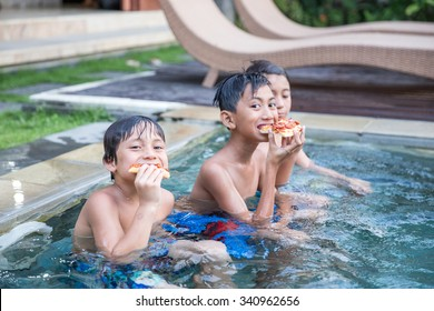 A portrait of three boys enjoying the pool while eating pizza