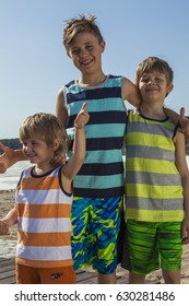 Portrait of three brothers thumbs up on the beach