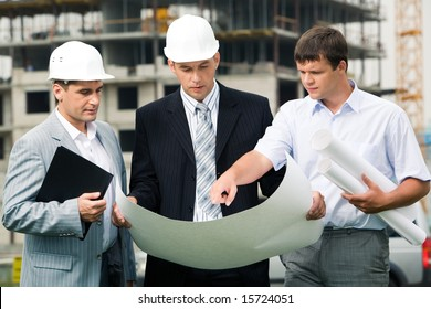 Portrait of three builders standing at building site and discussing new project held by one of men