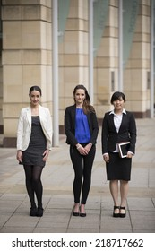 Portrait of three business women standing in a row. Interracial group of business women.
