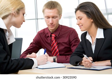 Portrait of three businesspeople discussing new project