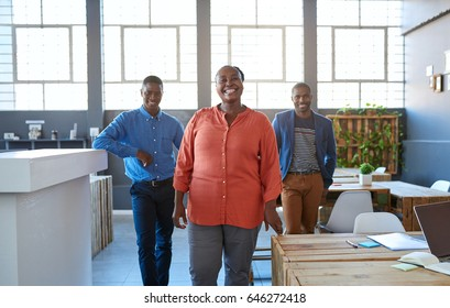 Portrait of three casually dressed young African businesspeople smiling confidently while standing together in a large modern office