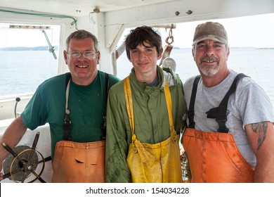 Portrait of three caucasian lobster-men in boat, Maine, USA