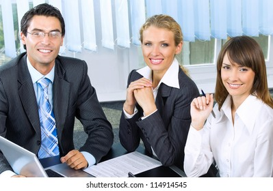 Portrait of three cheerful businesspeople at office