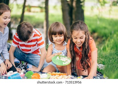 Portrait of three Children having fun in the garden in summer. They are laughing while they look at camera. Shot with flare