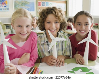 Portrait of three children looking to camera with paper windmills illustrating alternative energy in a school classroom