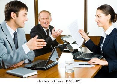 Portrait of three colleagues sitting in the office and discussing new business ideas looking at each other