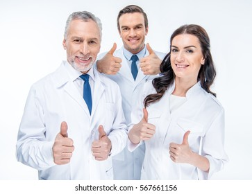 Portrait of three confident doctors smiling and showing thumbs up isolated on white