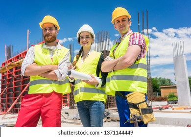 Portrait of three confident and reliable young employees, a female architect and two blue-collar workers, looking at camera while posing on the construction site