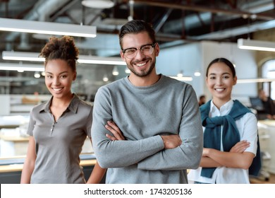 Portrait of three co-workers in casual wear. Two women and man smiling at camera, while standing in working space. Teamwork concept. Horizontal shot. Front view. Selective focus