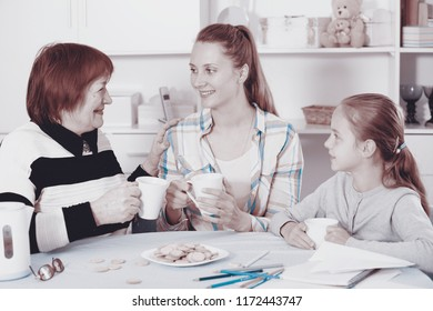 Portrait of three different ages womans sitting at the table with cups of tea