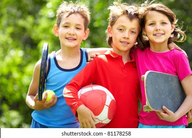 Portrait of three embracing children with sports equipment
