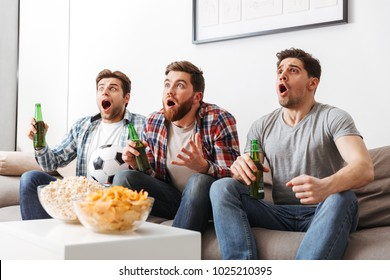 Portrait of three excited young men watching football while sitting at home, drinking beer and eating snacks