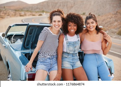 Portrait Of Three Female Friends Sitting In Trunk Of Classic Car On Road Trip