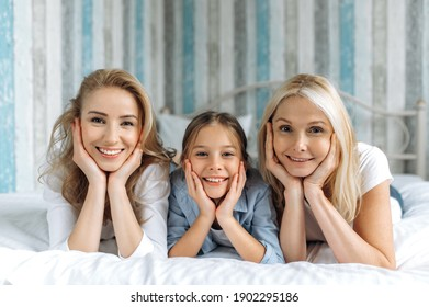 Portrait of three female generation. Happy caucasian grandmother, daughter and granddaughter are lying at home on the couch, looking at the camera and smiling. Family relationships and values