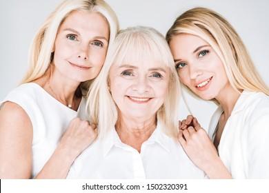 portrait of three generation blonde women isolated on grey
