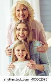Portrait of three generations of happy beautiful women looking at camera, hugging and smiling