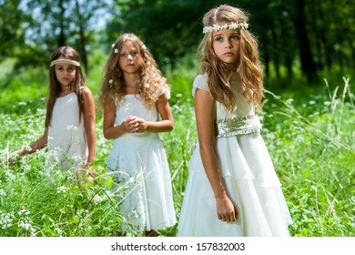 Portrait of three girl friends wearing white dresses in woods.