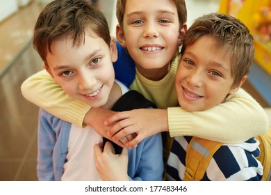 Portrait of three happy embracing boys