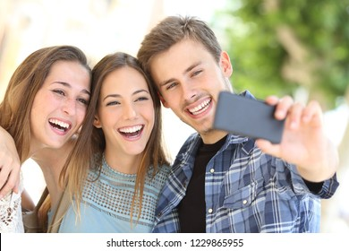 Portrait of three happy friends taking selfies together with a smart phone in the street