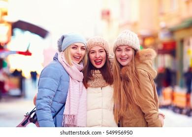 portrait of three happy girls, friends together on winter street