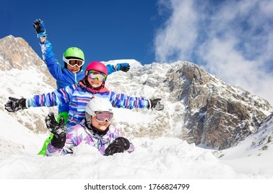 Portrait of three happy girls lay on top of each other in the snow smile, wave hands with mountains on background