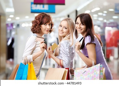Portrait of three happy girls in shop, with three credit cards in hands