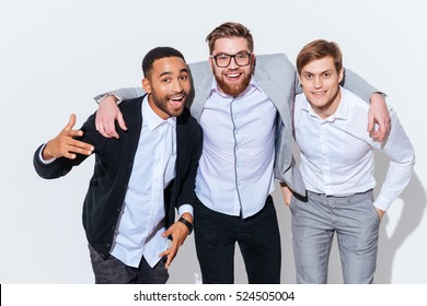 Portrait of three happy handsome young men standing together over white background