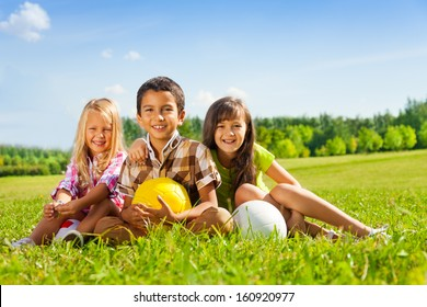 Portrait of three happy kids, boy and girls sitting in the sunny summer park holding sport balls
