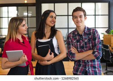 Portrait of three happy student standing together and smiling. Two women and man posing in classroom or office. Friendship concept