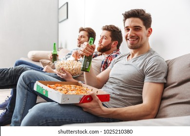Portrait of three happy young men watching football while sitting at home with beer and snacks indoors