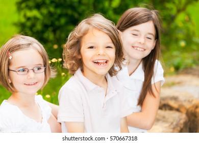 Portrait Of Three Kids In The Garden