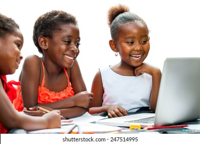 Portrait of three little African girls laughing at scene on laptop at desk.Isolated on white background.