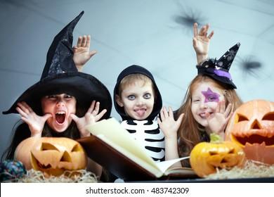 Portrait of three little children in Halloween fancy dresses making faces among pumpkins