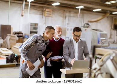 Portrait of three men standing and discuss in furniture factory