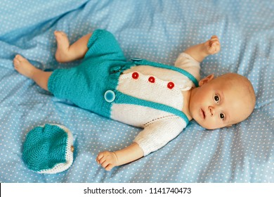 Portrait of a three months old baby boy on the bed on a blue blanket in nursery room. Flat lay.