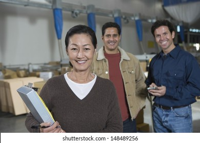 Portrait of three multiethnic workers in distribution warehouse