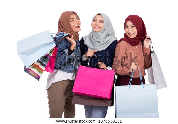 portrait of three muslim woman with shopping bag isolated over white background