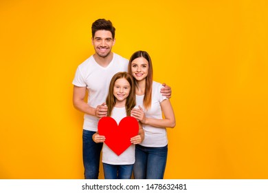 Portrait of three nice attractive charming lovely careful cheerful cheery tender amorous person holding in hands one big heart isolated over bright vivid shine yellow background
