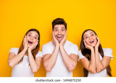 Portrait of three nice-looking attractive lovely cheerful cheery delighted amazed person having fun expecting dream isolated over bright vivid shine yellow background